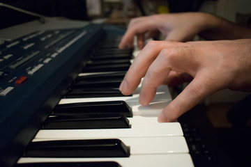 Man hands on the keyboard of the piano
