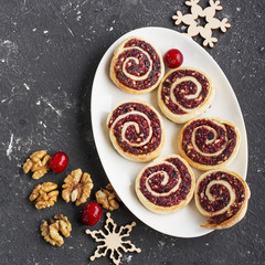 Cranberry nut swirl cookies on a white oval dish  New Year's treats with nuts, cranberries, fir branches. Top view