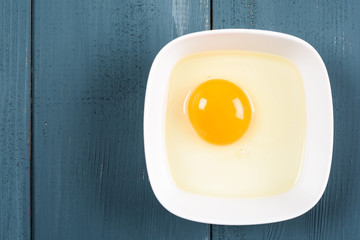 Yellow Egg Yolk In White Bowl On Wood Table
