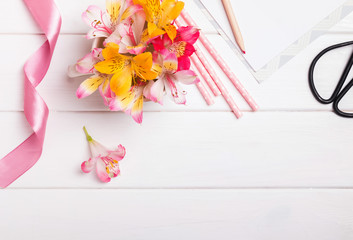 Flowers, paper straws and pink ribbon on white wooden table