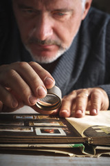 Man considers album of postage stamps trough the magnifying glass vertical