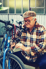 elderly man repairs bicycles
