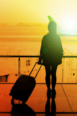 silhouette of young girl with luggage in the terminal at the air