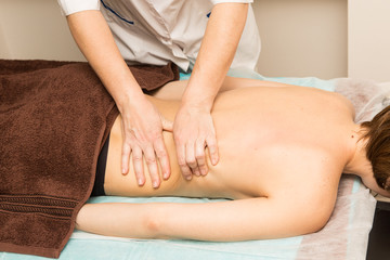 Image of a Masseuse giving relaxing back massage