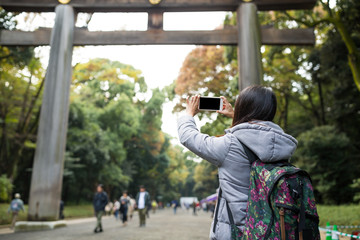 Woman take photo of Japanese torri in Meji Shrine