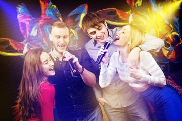 Group happy friends singing karaoke club