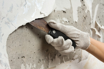 hand removing wallpaper from wall with spatula
