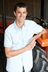 Portrait Of Male Agricultural Worker With Tractor