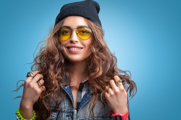 Closeup portrait of beautiful trendy hipster girl with curly hair and hands up smiling wearing red checkered shirt,denim vest and black beanie hat on blue background.Youth style,fashion.