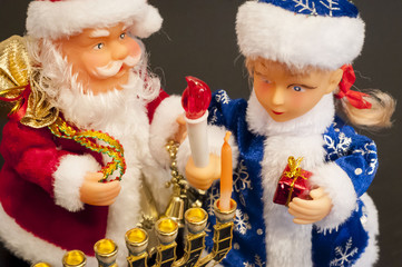 Toys Ded Moroz (Santa Claus) and Snegurochka lighting hanukkah candles. In December 2016 Jewish holiday Hanukkah coincides with Christmas and New Year.