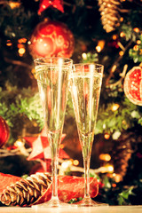Fototapete - Two glasses of champagne with Christmas tree background. Holiday