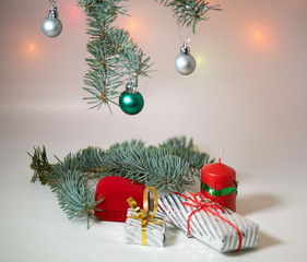 Branch of Christmas tree with balls, Christmas box and candle