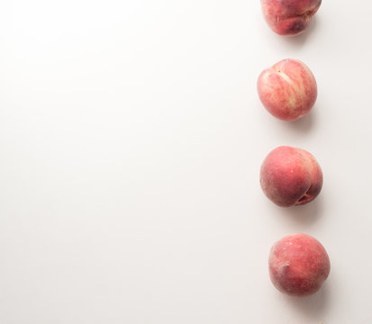 High angle view of white peaches arranged in a column on table with copy space to left