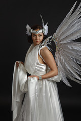 beautiful young model wearing a white dress with angel wings in