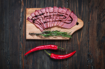 Sliced ham, chilli pepper, rosemary on a wooden board