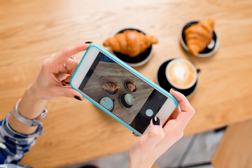 Photographing with smart phone coffee with croissants