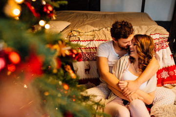 Couple in in pajamas resting on the floor next to the bed near the Christmas tree.