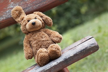 Childhood concept - cute vintage toy bear sitting on a banch
