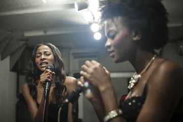 Young women singing in a recording studio