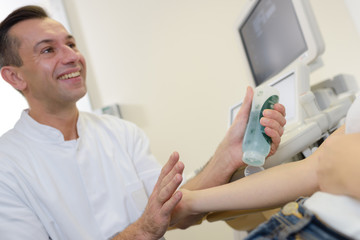 doctor putting gel on patients arm before ultrasound