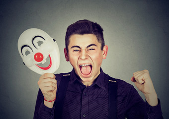Upset angry screaming man holding clown mask expressing cheerfulness