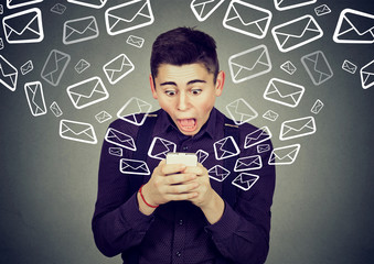 shocked man receiving messages from smartphone email icons flying away