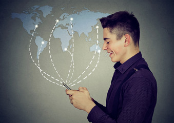 man using smartphone browsing internet on a worldwide map background