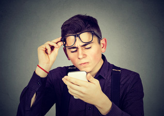 man with glasses having trouble seeing cell phone vision problems