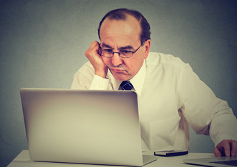 Annoyed bored middle aged man learning how to use computer