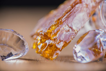 Piece of cannabis oil concentrate aka shatter with glass rig and
