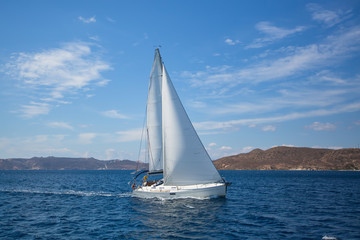 Luxury yacht at regatta. Sailing in the wind through the waves at the Aegean Sea.