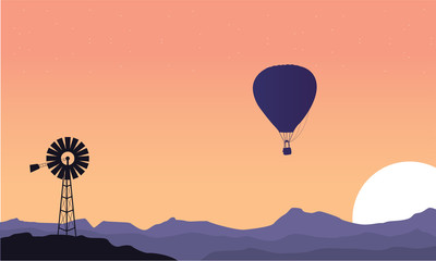 Silhouette of windmill and air balloon scenery