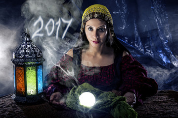 Female fortune teller doing a psychic reading with a cystal ball predicting the future of 2017.  The image is an illustrative editorial of the new year.