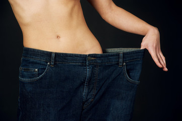 beautiful young woman with big jeans weight loss after the diet . On a dark background