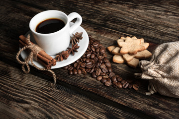 Coffee composition with black coffee, cinnamon and cookies on the old wooden table