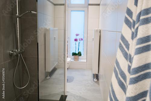 dusche mit glasabtrennung in einem schmalen badezimmer\
