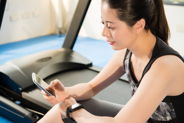 asian woman rest on treadmill use smartphone and smartwatch
