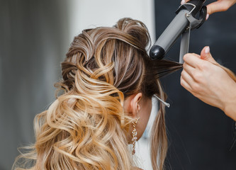 Closeup hairdresser coiffeur makes hairstyle. Wall mural