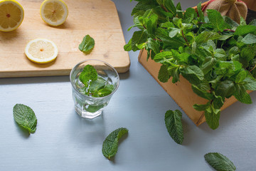 An ingredients for peppermint tea on light blue rustic table, lemon slices on chopping board,fresh mints in wooden box with peppermint leaves laying on table, healthy drink for winter,release stress
