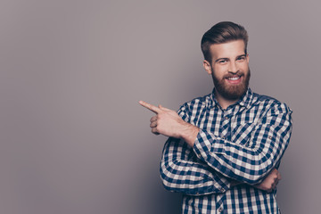 Cheerful handsome  stylish man showing direction and pointing wi Wall mural