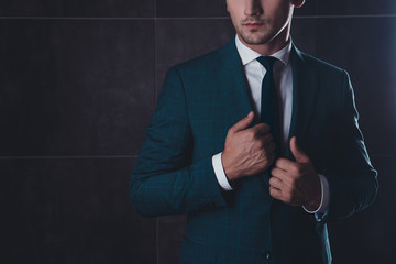 Close up of serious young businessman touching his suit
