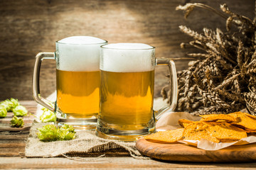 Two beer mugs with hops and chips on boards on linen cloth