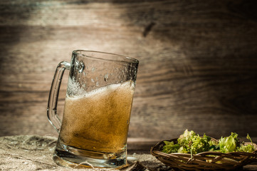 Beer spills from cup on empty wooden background
