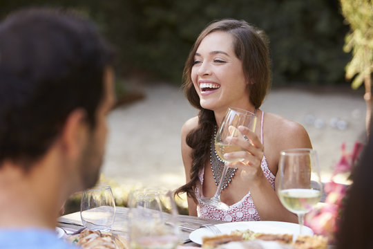 Smiling young woman holding a glass of wine at a party