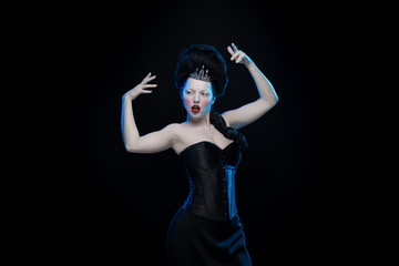 brunette woman with high hair, a tiara and a corset in old style on a black background