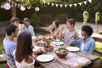 Friends Eating And Drinking Around Table At Outdoor Party