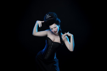 portrait of the actress brunette woman with high hair, crown and corset in old style on a black background