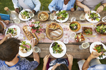 Overhead view of friends enjoying lunch and wine on wooden table outdoors