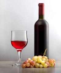 Виноградное красное вино в стеклянном бокале, гроздь винограда и бутылка вина для праздника.\ Натуральное виноградное вино для праздника, для здорового образа жизни.