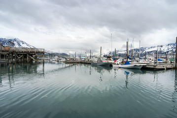 View of fishing boats moored at the port of Seward and snow covered mountains, Alaska